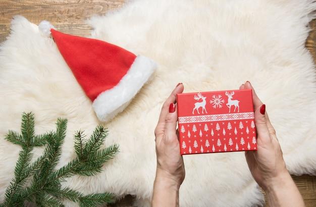 Feminino mão segurando a caixa de presente de natal. conceito de férias. inverno.