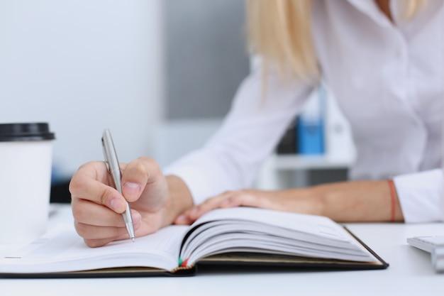 Feminino mão segurando a caneta prata pronta para fazer