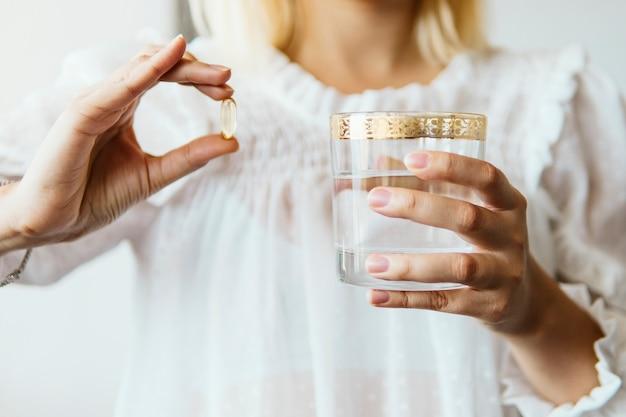 Feminino mão segurando a cápsula de suplemento de óleo de peixe omega 3 e copo de água