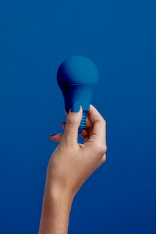 Feminino mão segurando a lâmpada azul clássica