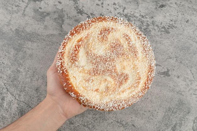 Feminino mão segurando a torta de maçã doce na superfície de mármore.