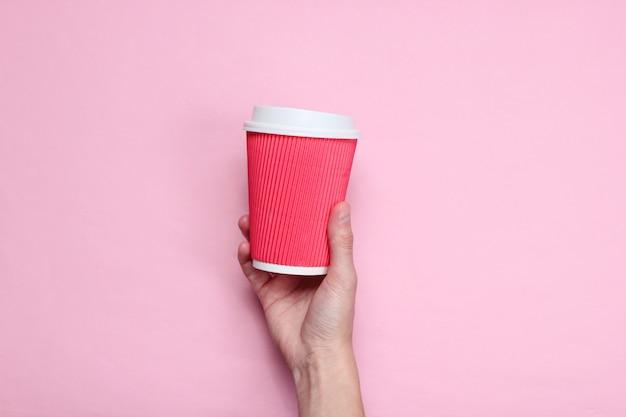 Feminino mão segurando a xícara de café de papel vermelho em rosa pastel. vista do topo