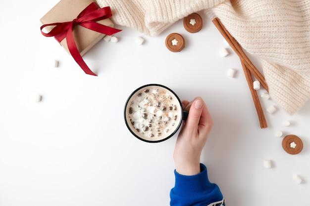 Feminino mão segurando a xícara de chocolate quente com marshmallow
