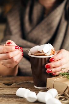 Feminino mão segurando a xícara de chocolate quente ou chocolate com marshmallow na mesa de madeira