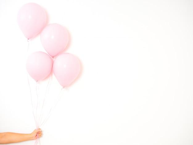 Feminino mão segurando balões rosa