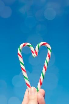 Feminino mão segurando bastões de caramelo em forma de um coração