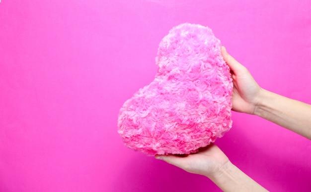 Feminino mão segurando coração de pelúcia em um fundo rosa.