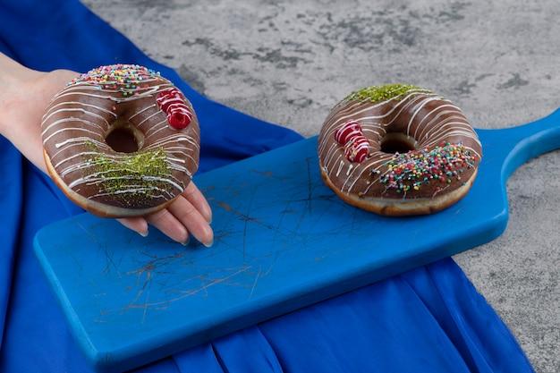 Feminino mão segurando donut de chocolate na superfície de mármore.