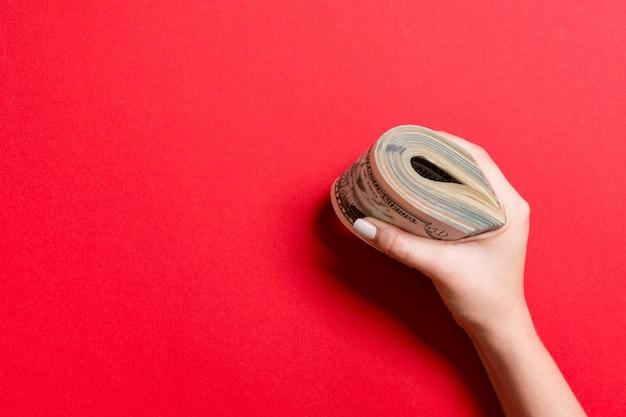 Feminino mão segurando firmemente um pacote de dinheiro. vista superior de fifry e vários dólares em fundo colorido. conceito de investimento com espaço de cópia