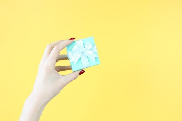 Feminino mão segurando lindo presente azul em fundo amarelo closeup. conceito de embrulho de presente