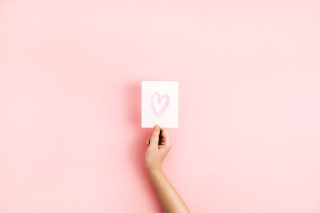 Feminino mão segurando o cartão com o símbolo do coração em fundo rosa pálido. flat lay, top view conceito de amor. Foto Premium
