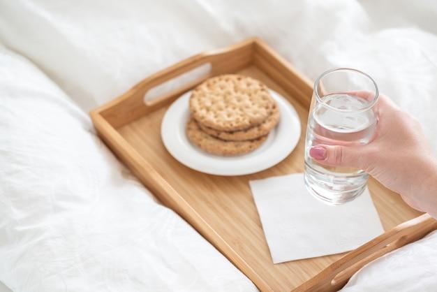Feminino mão segurando o copo de água sobre a bandeja com biscoitos na cama