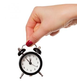 Feminino mão segurando o despertador em branco