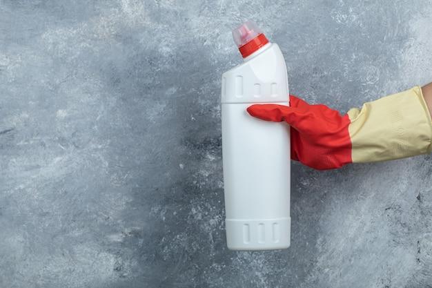 Feminino mão segurando o detergente no mármore.