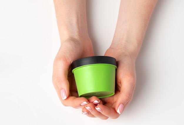 Feminino mão segurando o frasco cosmético em branco