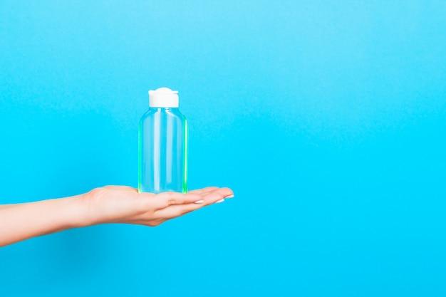 Feminino mão segurando o frasco de creme de loção isolado. a menina dá produtos cosméticos do tubo no azul