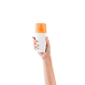 Feminino mão segurando o frasco de creme de loção isolado. a menina dá produtos cosméticos no branco