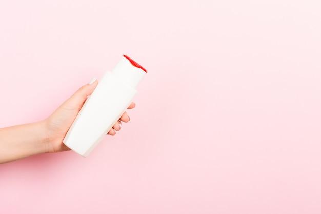 Feminino mão segurando o frasco de creme de loção isolado. menina dar produtos cosméticos tubo em fundo rosa