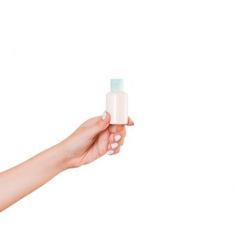 Feminino mão segurando o frasco de creme de loção isolado