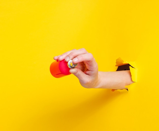Feminino mão segurando o frasco de perfume através de papel amarelo rasgado. conceito de moda minimalista