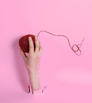Feminino mão segurando o novelo de linha através do papel rosa rasgado. conceito de medicina criativa minimalista