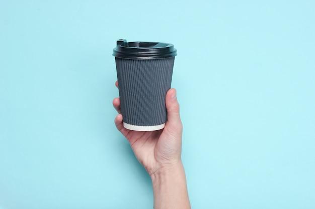 Feminino mão segurando o recipiente de café de papel preto pastel azul. vista do topo.