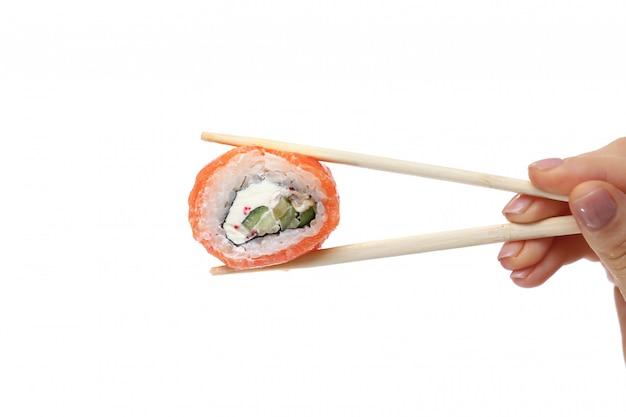 Feminino mão segurando o rolo de sushi com pauzinhos contra branco puro