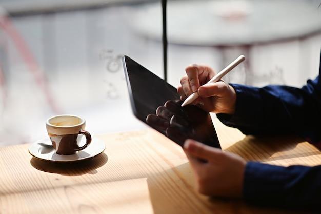 Feminino mão segurando o tablet de desenho no café