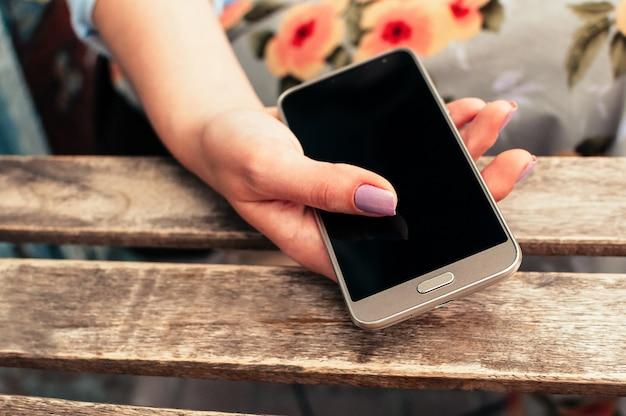 Feminino mão segurando o telefone inteligente com tela em branco, na mesa