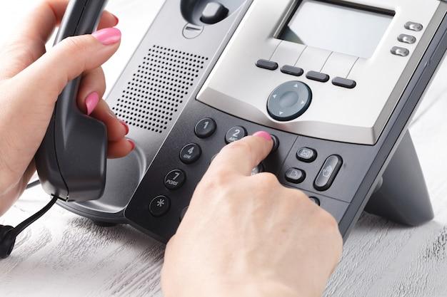 Feminino mão segurando o telefone receptor e número de discagem
