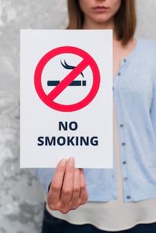 Feminino mão segurando papel com massagem não fumar