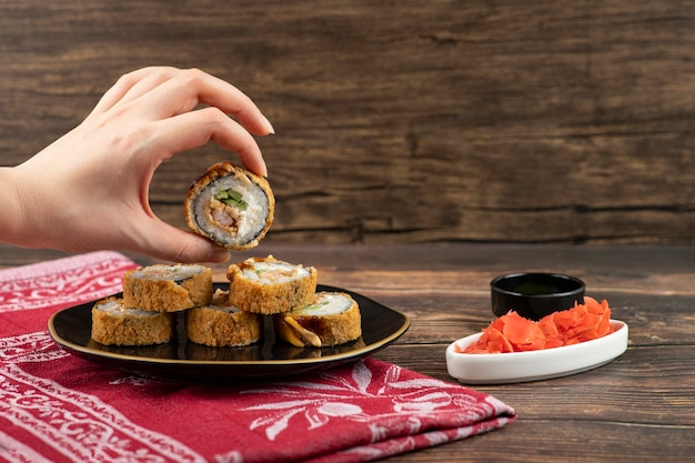 Feminino mão segurando rolo de sushi quente na superfície de madeira.