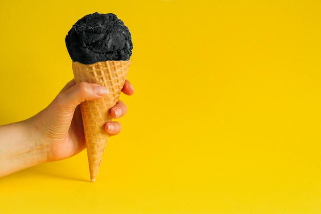 Feminino mão segurando sorvete de cone de waffle com carvão preto