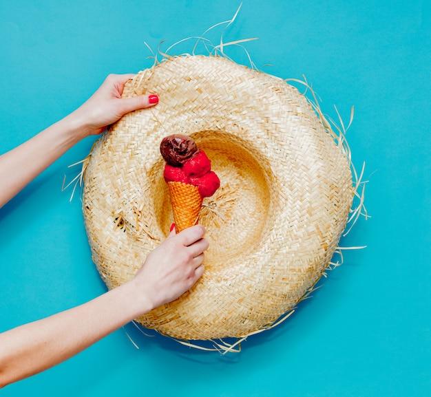 Feminino mão segurando sorvete de framboesa e chocolate com chapéu de palha