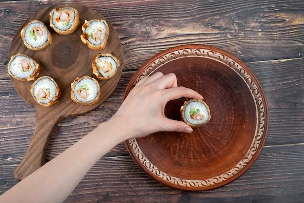 Feminino mão segurando sushi roll com camarão, abacate, queijo, omelete empanado.