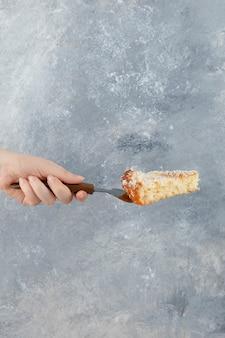 Feminino mão segurando torta doce na superfície de mármore.