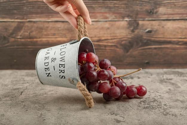 Feminino mão segurando um balde de metal de uvas vermelhas na mesa de mármore.