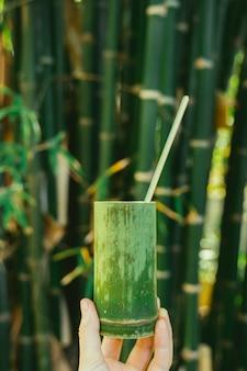 Feminino mão segurando um copo artesanal com madeira de bambu. recipientes naturais. reutilize e recicle copos orgânicos.