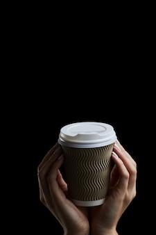 Feminino mão segurando um copo de papel de café no escuro