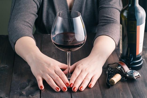 Feminino mão segurando um copo grande de vinho tinto