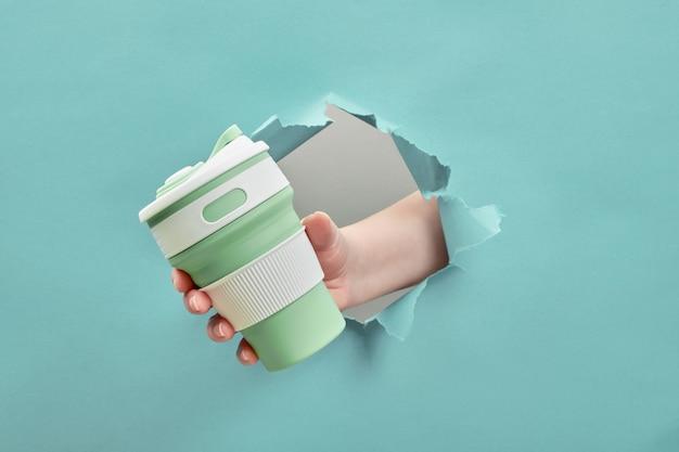 Feminino mão segurando um copo reutilizável de silicone através de um buraco rasgado. estilo de vida sustentável. conceito amigável de eco.