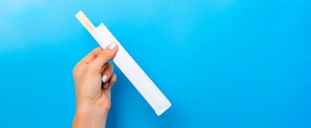 Feminino mão segurando um pacote com pauzinhos sobre fundo azul. conceito de sushi com espaço vazio para a sua ideia