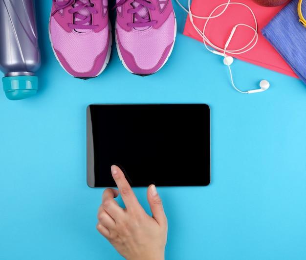 Feminino mão segurando um tablet eletrônico com uma tela preta em branco, ao lado dela é roupas de fitness