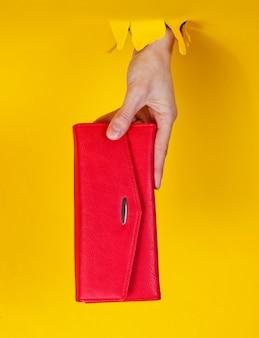 Feminino mão segurando uma carteira vermelha através de papel amarelo rasgado. conceito de moda criativa minimalista