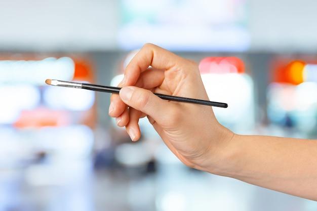 Feminino mão segurando uma escova de maquiagem profissional
