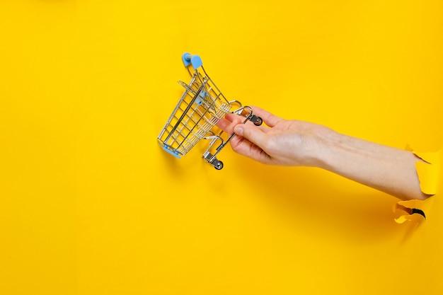 Feminino mão segure o mini carrinho de compras através de papel amarelo rasgado. conceito de compras minimalista