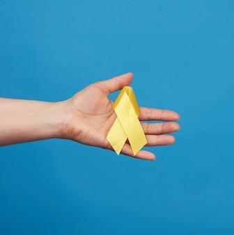 Feminino mão segure uma fita amarela na forma de um laço