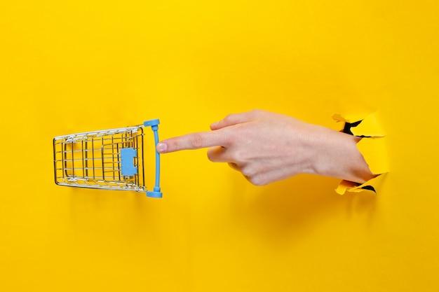 Feminino mão toca um mini carrinho de compras através de papel amarelo rasgado. conceito de compras minimalista