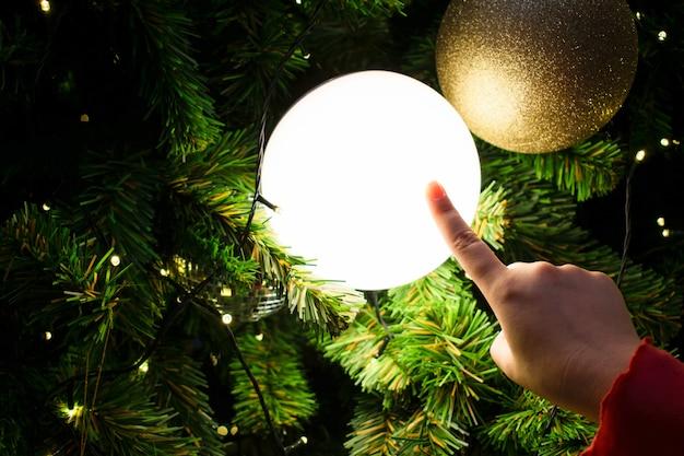 Feminino mão tocando uma bola de luz. árvore de natal decorada no tema prata e ouro.