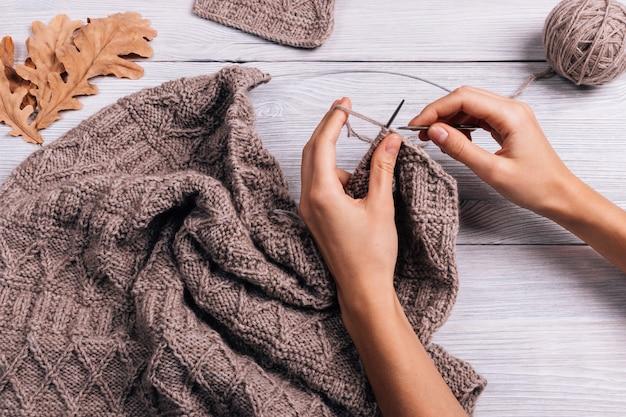 Feminino mão tricotar suéter de lã, vista superior